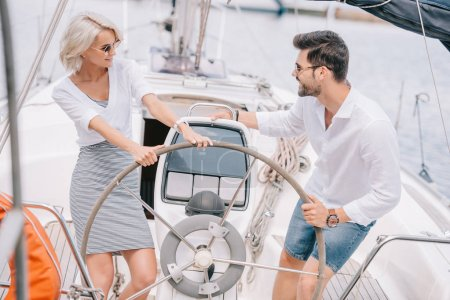 high angle view of happy young couple in sunglasses smiling each other on yacht