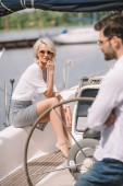 beautiful pensive girl in sunglasses sitting on yacht and man standing on foreground