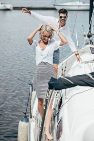 high angle view of happy young couple in sunglasses walking on yacht