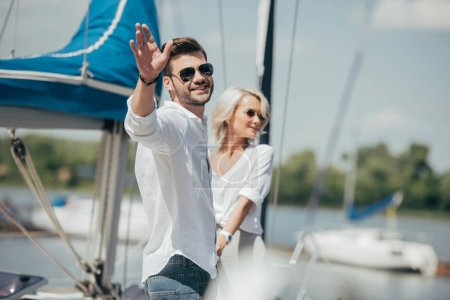 happy young man in sunglasses smiling at camera and waving hand while holding hands with beautiful girl on yacht