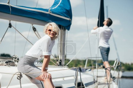 beautiful young woman in sunglasses smiling at camera on yacht