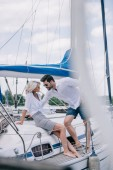 selective focus of beautiful young couple in sunglasses looking at each other on yacht