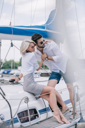 selective focus of young couple in love hugging and looking away on yacht