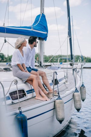 beautiful young couple sitting together on yacht and looking away