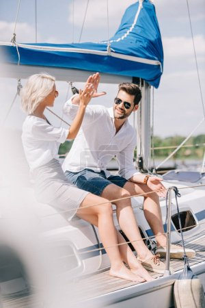 Photo for Happy young couple giving high five while sitting together on yacht - Royalty Free Image
