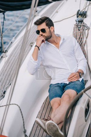 high angle view of pensive young man in sunglasses looking away while sitting on yacht