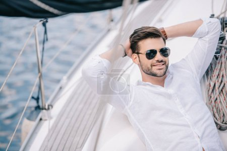 handsome smiling young man in sunglasses resting with hands behind head on yacht