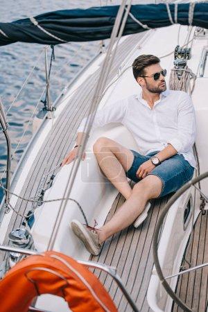 Photo pour Beau jeune homme à lunettes de soleil à la recherche de suite assis sur yacht - image libre de droit
