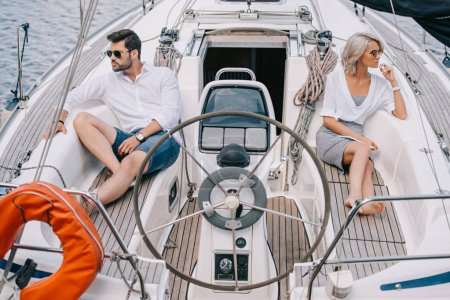 serious young couple in sunglasses looking away while sitting on yacht