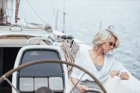 Photo for Young woman in sunglasses using digital tablet and checking wristwatch while sitting on yacht - Royalty Free Image