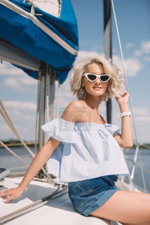 beautiful young blonde woman in sunglasses smiling at camera while sitting on yacht