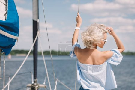 rear view of beautiful young blonde woman in sunglasses looking away while standing on yacht
