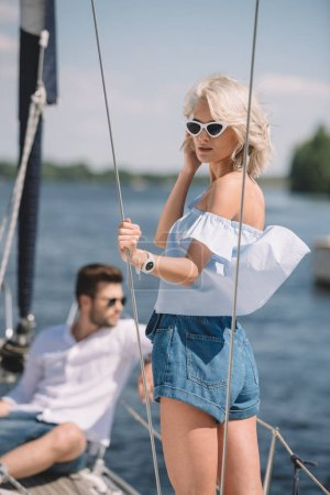 beautiful young woman in sunglasses standing on yacht while man sitting behind