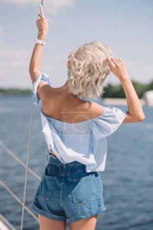 Photo pour Vue arrière de la jeune femme blonde regardant loin tout en se tenant sur le yacht - image libre de droit