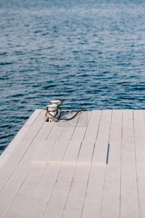 empty wooden pier and blue water at summer day