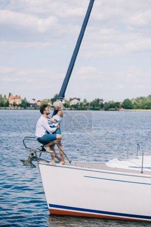 Photo pour Vue latérale du beau jeune couple heureux assis et des caresses sur yacht - image libre de droit