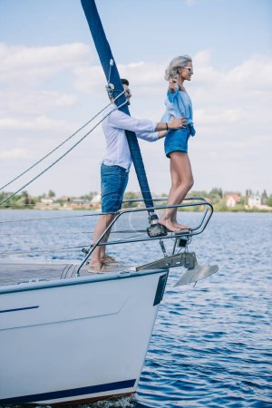 side view of happy young couple in sunglasses spending time together on yacht