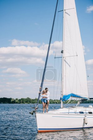 beautiful young couple hugging while spending time together on yacht