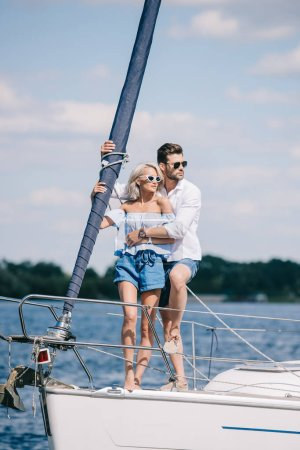 beautiful young couple in sunglasses looking away while hugging on yacht