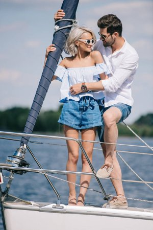 happy young couple in sunglasses hugging on yacht