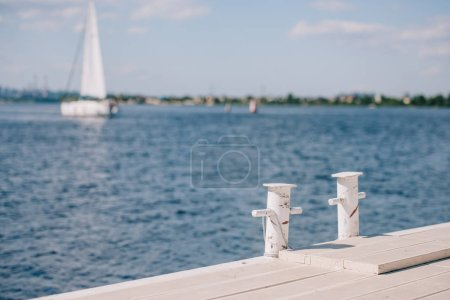 empty wooden pier and yacht on background at summer day
