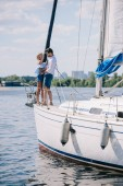 beautiful stylish couple hugging while standing together on yacht
