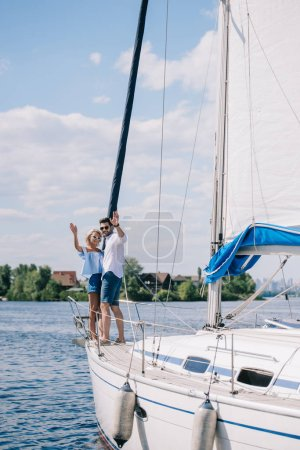 beautiful young couple waving hands while standing together on yacht