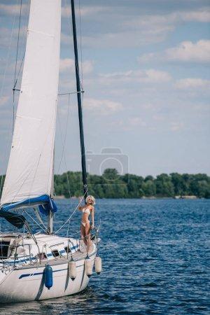 Photo pour Belle jeune femme blonde en bikini se tenant debout sur yacht - image libre de droit