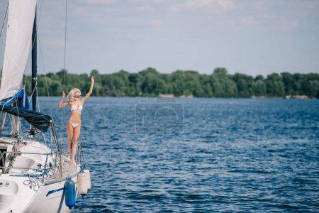 beautiful blonde woman in bikini standing on yacht