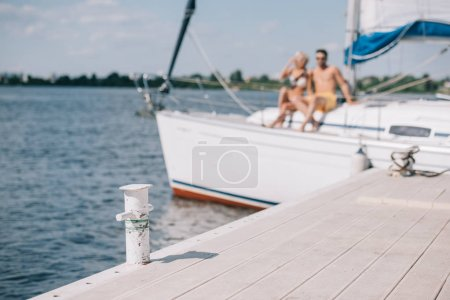 selective focus of wooden pier and young couple on yacht behind