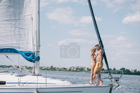 full length view of beautiful young couple in swimwear and sunglasses standing together on yacht