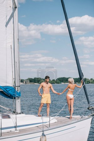 beautiful young couple in swimwear holding hands while standing together on yacht
