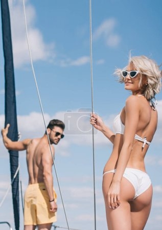 happy young couple in swimwear and sunglasses spending time together on yacht