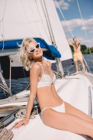 beautiful smiling girl in bikini and sunglasses sitting on yacht