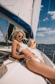 attractive young woman in bikini and her boyfriend behind on yacht