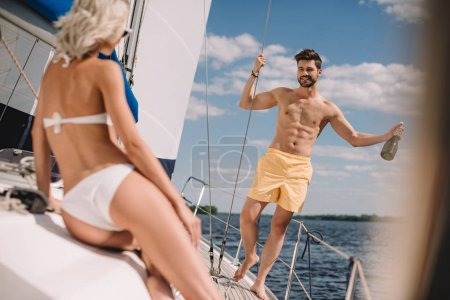 handsome shirtless man with bottle of champagne and his girlfriend on yacht
