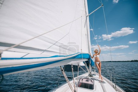 Photo for Distant view of attractive young woman in swimwear standing on yacht - Royalty Free Image