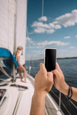 cropped image of man taking picture of girlfriend on smartphone on yacht