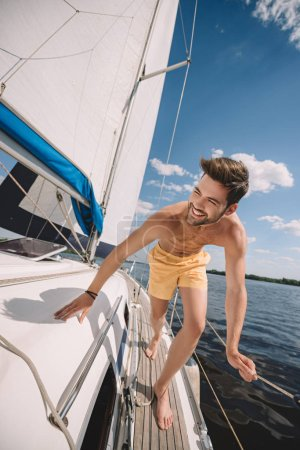 Photo for Smiling shirtless man in swim trunks running on yacht - Royalty Free Image