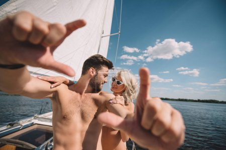 selective focus of shirtless man gesturing by hands and talking to smiling girlfriend on yacht