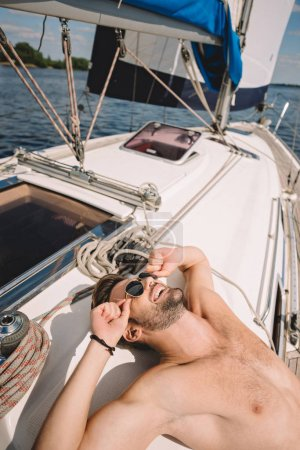 smiling shirtless muscular man in sunglasses having sunbath on yacht