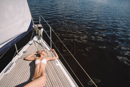high angle view of attractive young woman in swimwear having sunbath on yacht