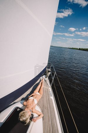 elevated view of young woman in bikini relaxing and having sunbath on yacht