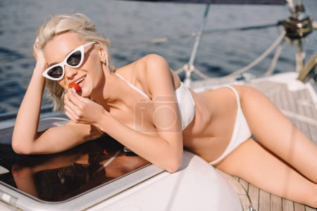 happy young woman in sunglasses and bikini eating strawberry and relaxing on yacht