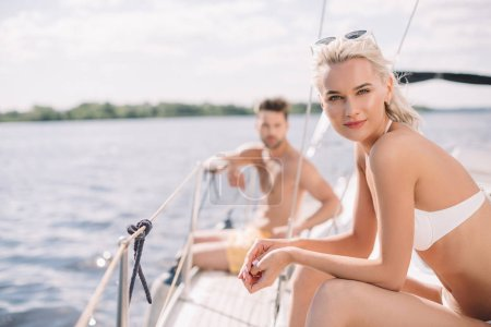 selective focus of young attractive woman in bikini and her boyfriend sitting behind on yacht
