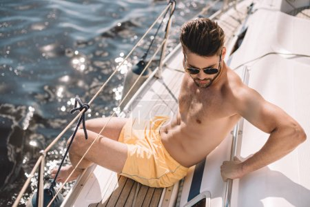 shirtless muscular man in swim trunks and sunglasses having sunbath on yacht