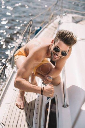 Foto de Sonriente hombre sin camisa en gafas de sol tirando de la cuerda en el yate - Imagen libre de derechos