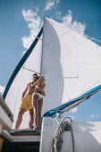 low angle view of shirtless man in sunglasses embracing girlfriend in bikini on yacht