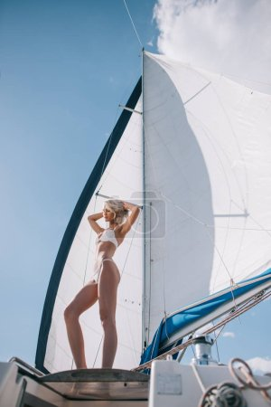 low angle view of beautiful young woman in bikini posing on yacht