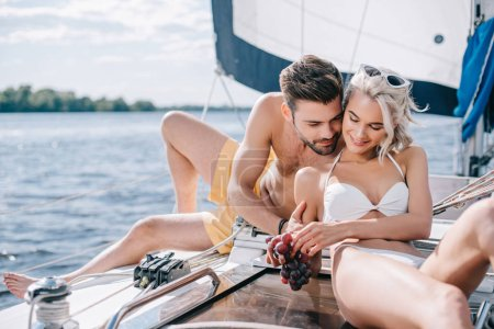 Photo for Happy young couple in swimwear relaxing and eating grapes on yacht - Royalty Free Image